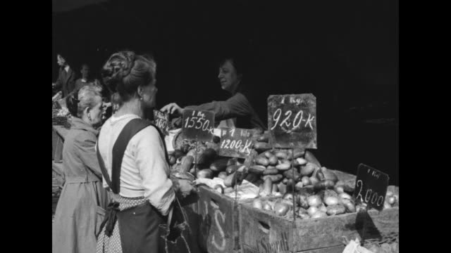 men emptying large bag stuffed with many square bundles of austrian crowns / vs women shoppers at produce stand with inflated price tags vs potatoes... - インフレ点の映像素材/bロール