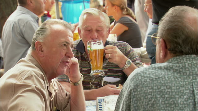 cu men enjoying beer at beer garden, viktualienmarkt, munich, bavaria, germany - gente comune video stock e b–roll