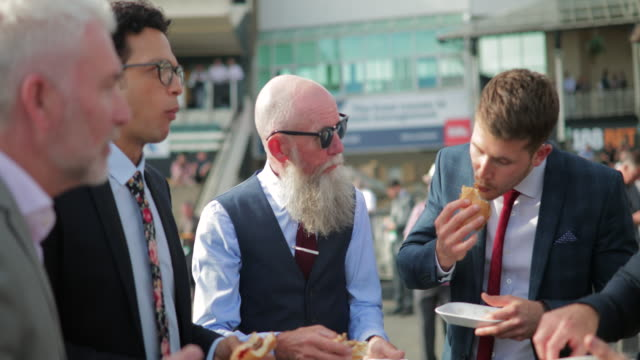 men enjoying burger, chips and beer outside - horse racing stock videos & royalty-free footage