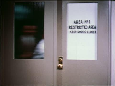 """vídeos y material grabado en eventos de stock de 1957 men entering + exiting door marked """"area no.1 - restricted area - keep door closed"""" - 1957"""