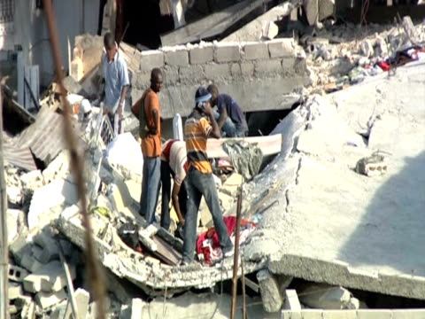 vídeos de stock e filmes b-roll de men examine rubble hoping to find trapped victims following devastating earthquake haiti - hispaniola
