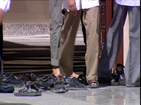 men exit mosque after prayers putting on socks and sandals dubai - sandal stock videos and b-roll footage
