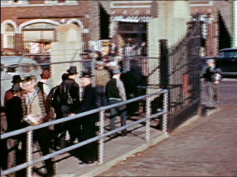 vidéos et rushes de 1941 pan men exiting gates of factory to street with beer billboards / chicago / industrial - prelinger archive
