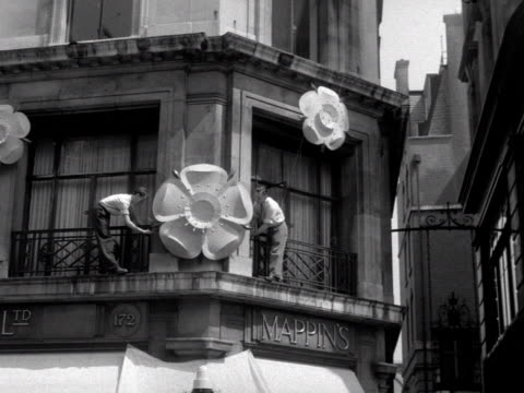 Men fastening large models of Tudor roses onto the exterior of a shop on Regent Street to celebrate the coronation of Elizabeth II 1953