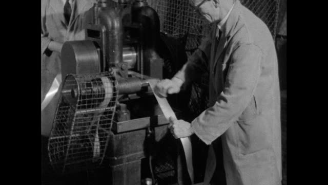 men feed gold through roller; 1956 - gold leaf stock videos & royalty-free footage