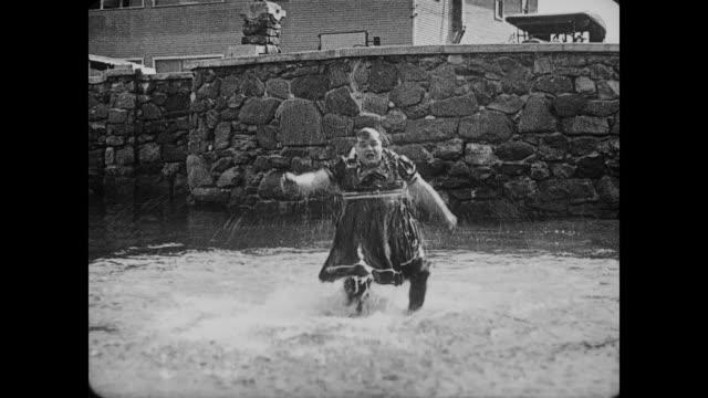 stockvideo's en b-roll-footage met 1917 men fight on beach (fatty arbuckle & al st. john) until they both end up fighting in the ocean - 1917