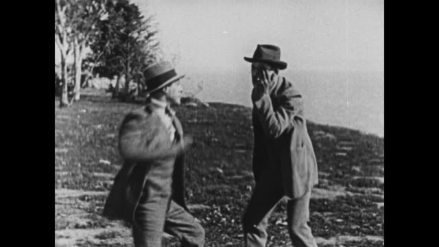 vidéos et rushes de 1924 men fight on cliff top until one is pushed over edge, clings to side - pushing