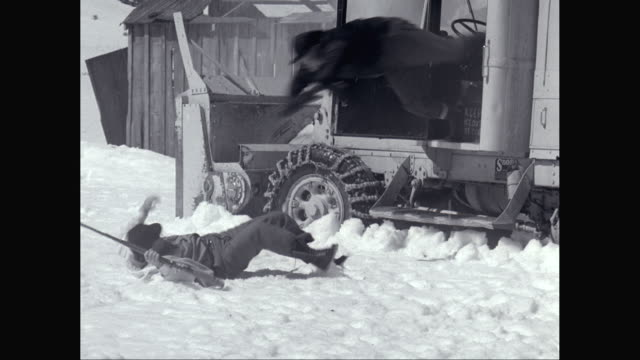 MS PAN Men fighting with rifle in snow field, truck plowing snow moving toward / United States