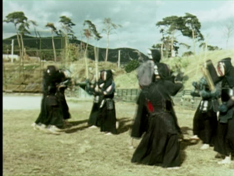 ws pan men fighting with sticks, tokyo, japan / audio - 1960年点の映像素材/bロール