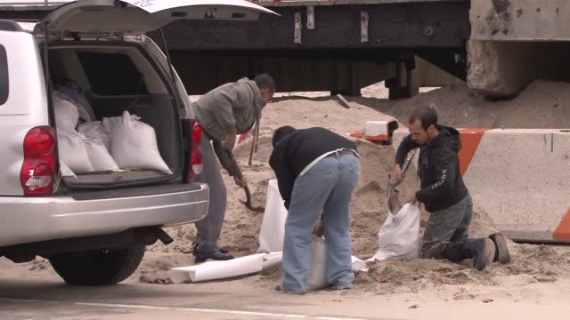 men fill sandbags and load them into an suv - sandbag stock videos & royalty-free footage