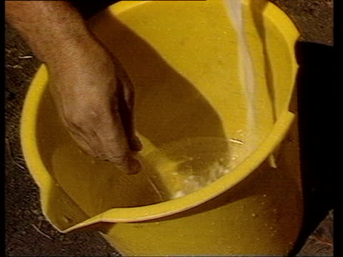 men filtering liquid to make cocaine/ cu mixing and filtering into bucket/ cu collecting past on handkerchief/ cu mixing liquid in bucket/ cu paste... - 麻薬点の映像素材/bロール