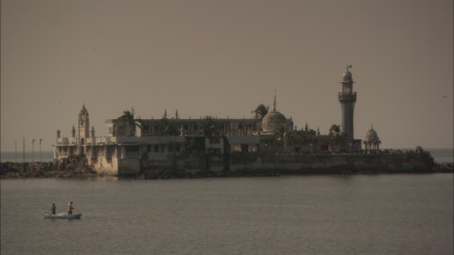 Men fish from small boat in front of Haji Ali Mosque Worli district Mumbai Available in HD.