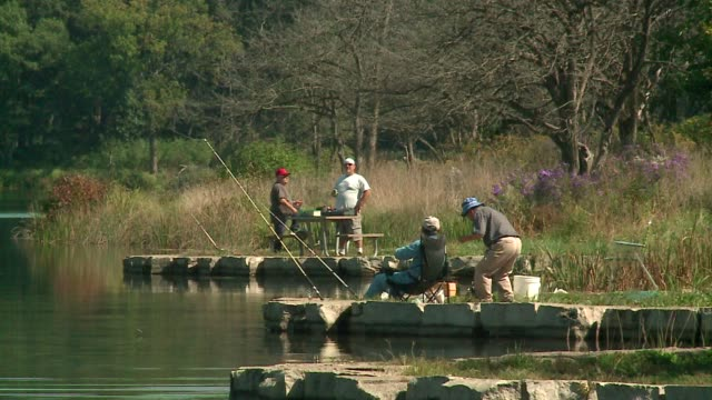 men fishing on a lake on an early fall day at cook county forest preserve on september 23, 2015. - illinois stock videos & royalty-free footage