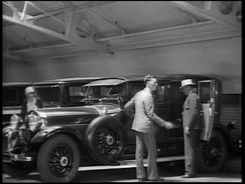 b/w 1928 men + flapper looking at new lincoln cars in lot / newsreel - car showroom stock videos & royalty-free footage
