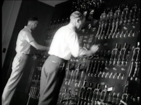 men flip levers inside the hoover dam control room - hoover staudamm stock-videos und b-roll-filmmaterial