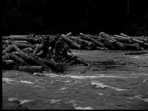 1927 B/W MONTAGE WS PAN Men freeing logs trapped along river, Ontario, Canada