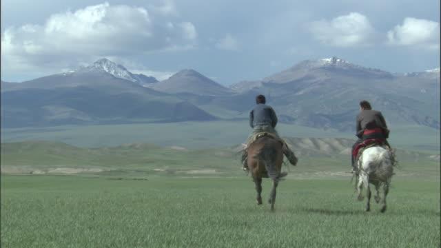 men gallop horses across grassland under a stormy sky, bayanbulak grasslands. - galoppieren stock-videos und b-roll-filmmaterial