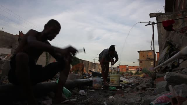 MS Men gather in an area where homes were recently destroyed near Maracana stadium as part of favela evictions ahead of the World Cup and Olympics on...