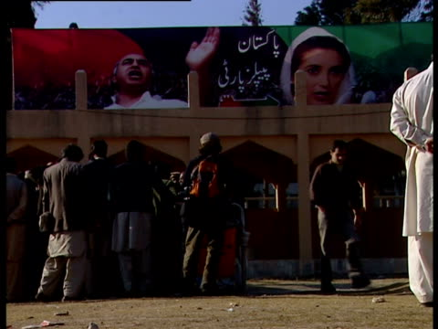 men gathered outside building with poster of benazir bhutto - poster stock videos & royalty-free footage