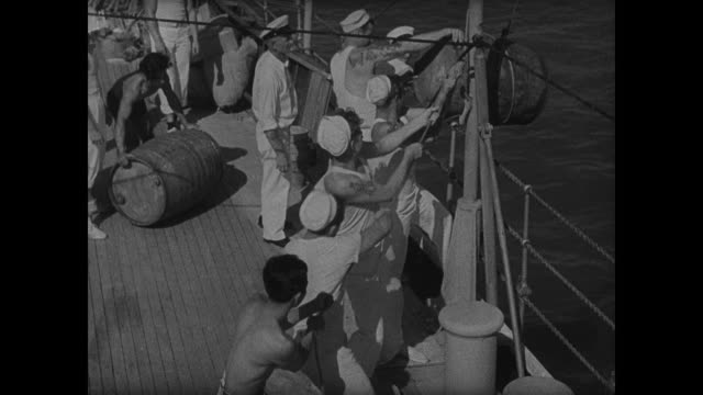 men getting off cutter & into supply filled boats moving away from cutter toward island sailors hoisting water barrel boats landing on island men... - hoisting stock videos & royalty-free footage