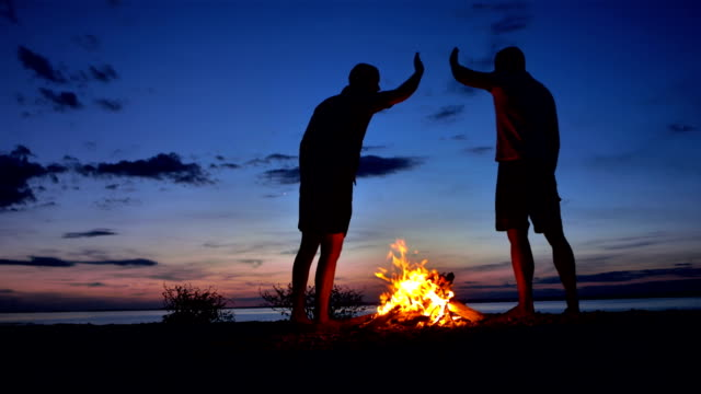 w の男性、ハイファイブで挨拶するには、焚き火 - adults only videos点の映像素材/bロール