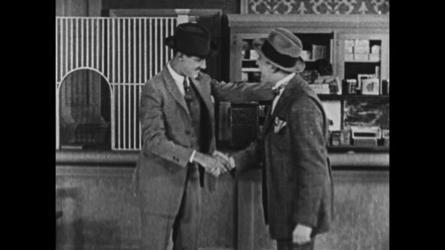 vídeos de stock, filmes e b-roll de 1924 men greet each other, excitedly shaking hands - dando a mão