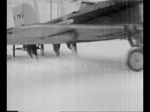 """men guide tail and wings of plane as it backs up through snow; plane is labeled """"us mail express"""" / pilot waves from cockpit of plane as it taxis... - 航空便点の映像素材/bロール"""