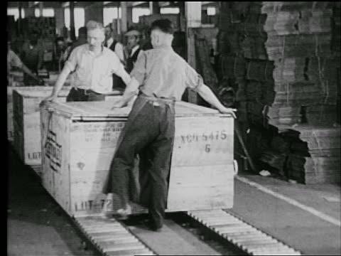 b/w 1927 2 men hammering crate / industrial - car plant stock videos & royalty-free footage