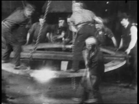 b/w 1904 men hammering large metal ring in westinghouse factory / pennsylvania / newsreel - pennsylvania stock videos & royalty-free footage
