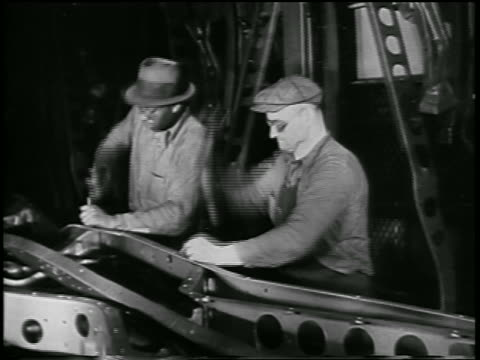 vidéos et rushes de b/w 1932 men hammering parts in ford car factory / industrial - ford