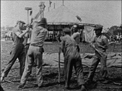 B/W 1928 men hammering stake in for circus tent / documentary