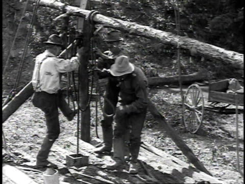 1923 reenactment men hand-drilling with spring pole / titusville, pennsylvania, united states  - industria petrolifera video stock e b–roll