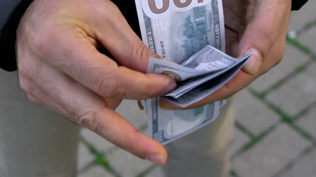 Men hands hold and counting dollar banknotes