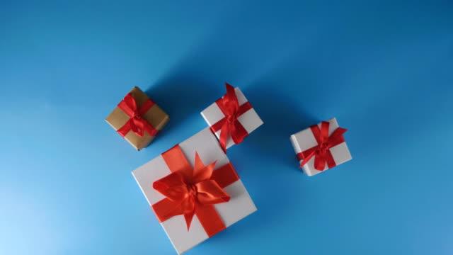 stockvideo's en b-roll-footage met mannen handen een cadeau op een blauwe achtergrond plaatsen - verjaardagskado