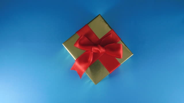 men hands put a gift on a blue background - giving stock videos & royalty-free footage