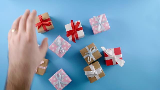 vídeos de stock, filmes e b-roll de mãos de homens, colocar um presente em um fundo azul - recebendo