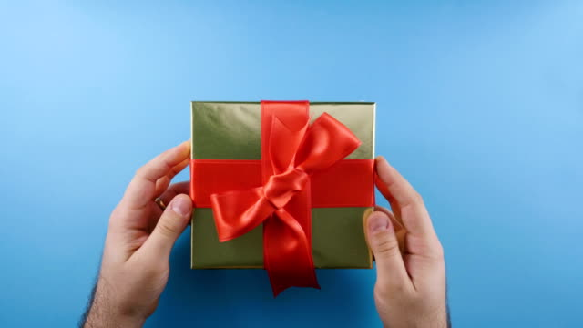 Men hands put a gift on a blue background