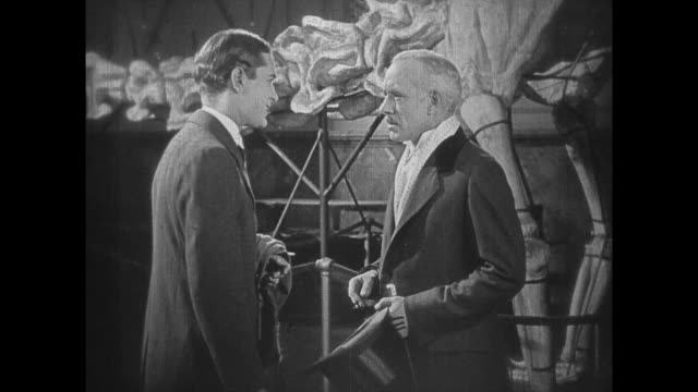 1925 men have conversation as crowd file past dinosaur exhibit - 1925 stock videos & royalty-free footage