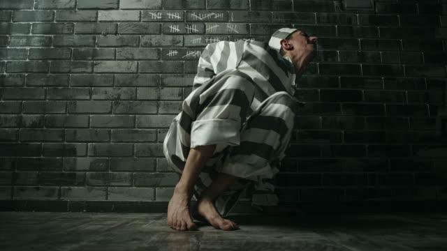 vídeos y material grabado en eventos de stock de hombres que tienen dolor abdominal en la celda de la prisión - torture