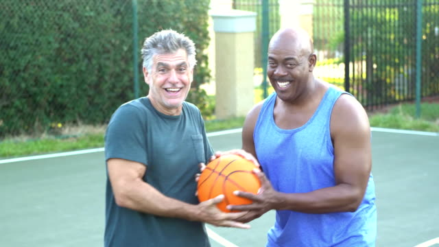 men having fun on basketball court fighting over ball - 50 59 years stock videos & royalty-free footage