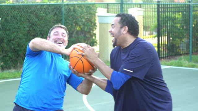 vídeos de stock, filmes e b-roll de homens que têm o divertimento na luta da corte de basquetebol sobre a esfera - esporte de equipe