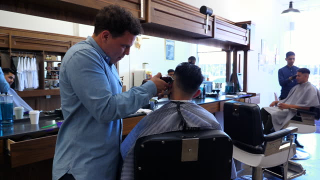 ms men having hair cut in barber shop - barber chair stock videos & royalty-free footage
