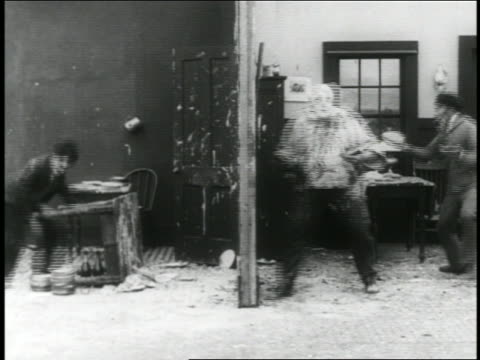 b/w 1916 3 men having pie fight on movie set / short - 1916 stock videos & royalty-free footage