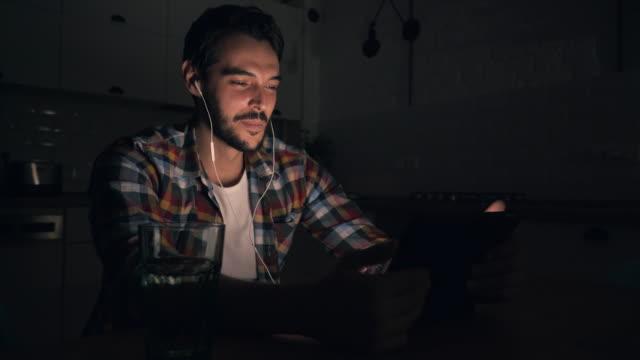vídeos de stock, filmes e b-roll de homens, tendo a chamada de vídeo usando um tablet digital. - meia noite