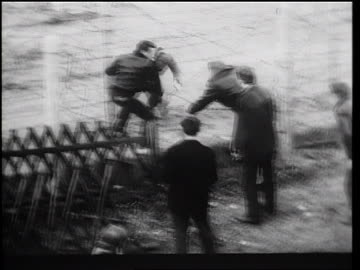 vidéos et rushes de men helping another man escape thru barbed wire fence of berlin wall / germany / newsreel - 1961