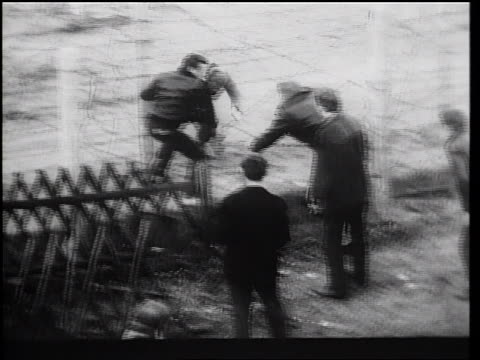 vídeos de stock e filmes b-roll de b/w 1961 men helping another man escape thru barbed wire fence of berlin wall / germany / newsreel - 1961