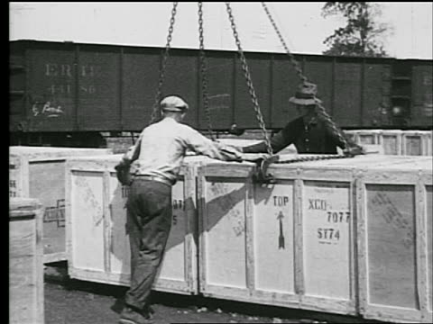 b/w 1927 2 men helping attach crane to large crate outdoors / industrial - car plant stock videos & royalty-free footage