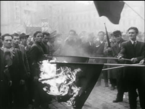 B/W 1956 men hold burning Soviet flags on poles in middle of crowd / Hungarian uprising