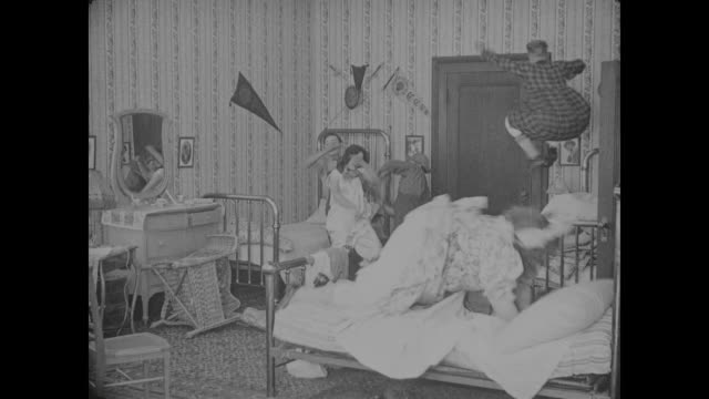 1917 men (buster keaton) hold girl (alice lake) as clerk (al st. john) and butcher (fatty arbuckle) fight in dorm room - fatty arbuckle stock videos and b-roll footage