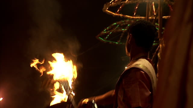 Men hold pans with flames in a ritualistic dance.